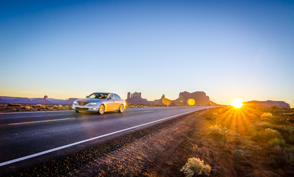 A car drives along an empty road in front of Utah's Monument Valley - Photo by Author