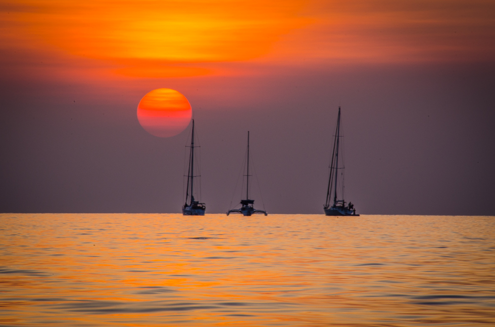 Sunset over a group of sail boats - Photo by Author