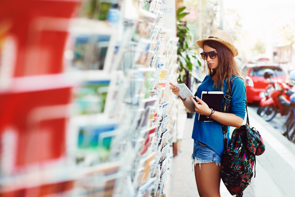 girl-on-vacation-looking-at-postcards