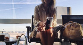 Woman at airport drinking coffee.