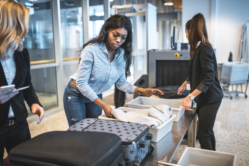 Female passengers going through security check. Security staff checking luggage of travelers. They are at airport. (Female passengers going through security check. Security staff checking luggage of travelers. They are at airport., ASCII, 115 componen