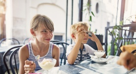 Kids are eating delicious italian ice cream at cafe in Rome, Italy. Kids aged 10 and 7 are visiting Rome on summer vacations.