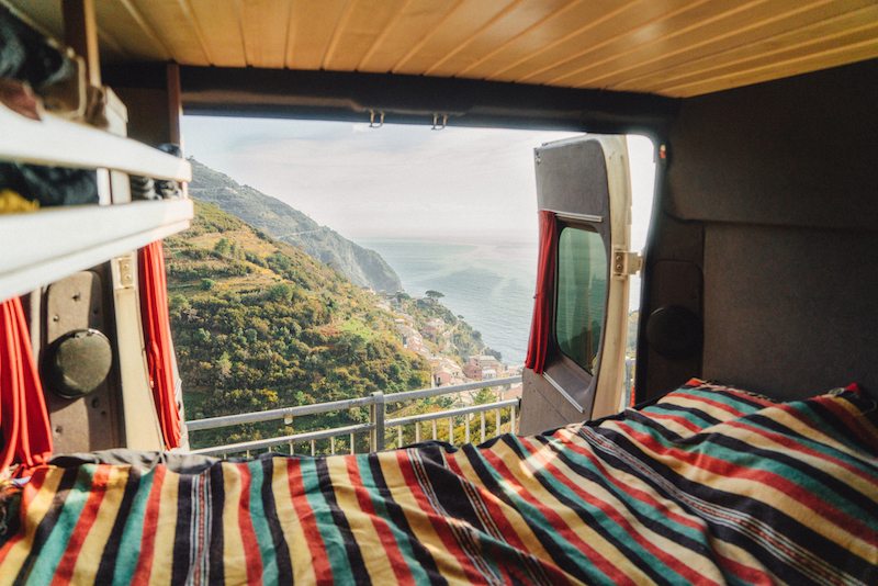 Camper van bed with view on Cinque Terre seaside in Italy