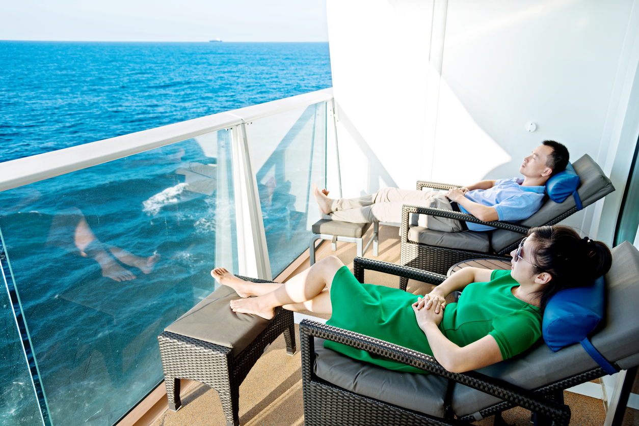Young couple relaxing in balcony with scenic sea views on a cruise ship.