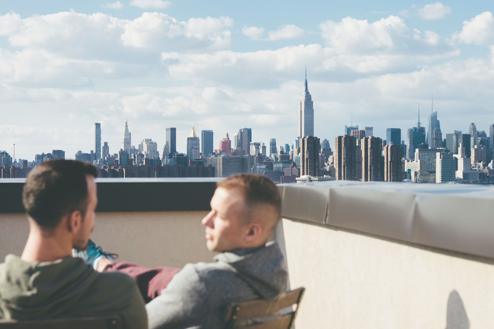 Gay Men Friends Hanging Out On A Rooftop Enjoying The View In New York