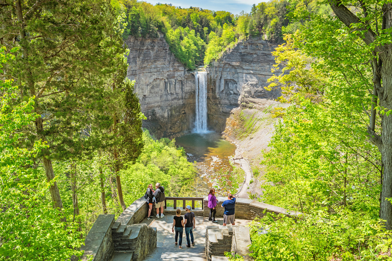 People look at Taughannock Falls near Ithaca, Finger Lakes region, upstate New York, USA on a sunny day.