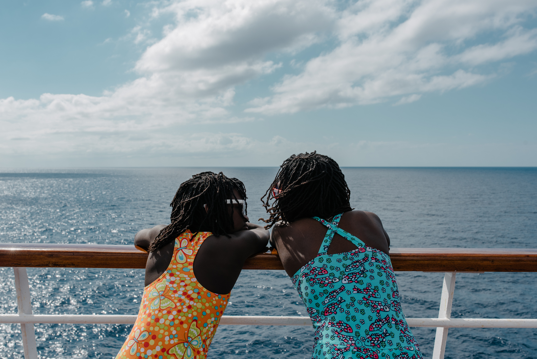 Two black girls in swimming suit on the deck of a sailing cruise ship watching the ocean