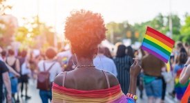 black woman holding Pride flag in a crowd