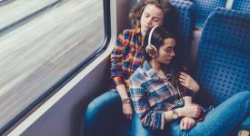 lesbian couple sleeping on a train
