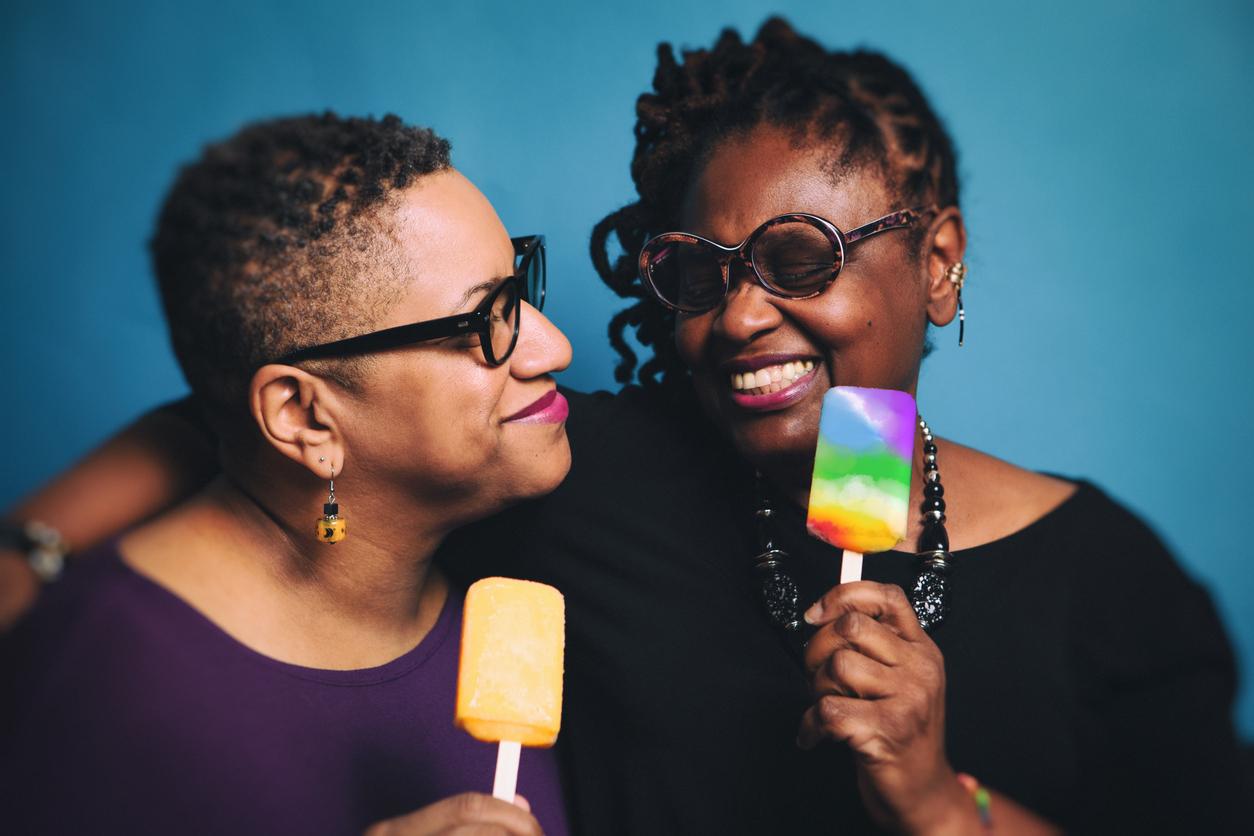 Mature, fun lesbian couple eating popsicles.