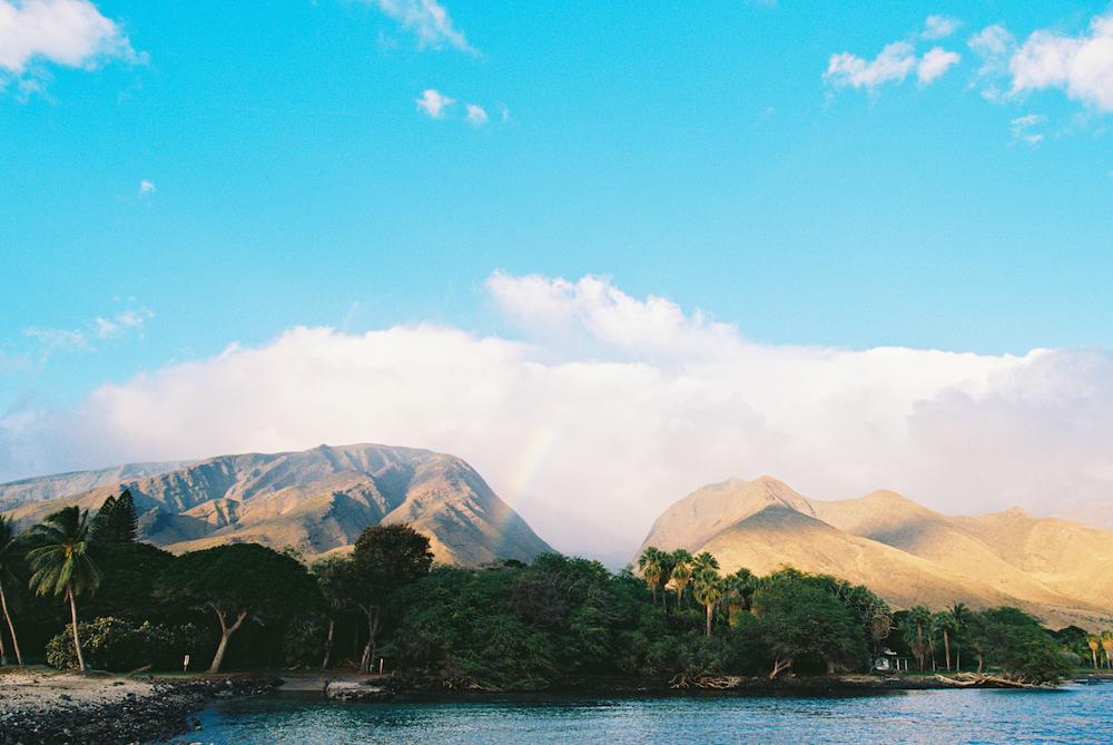 rainbow over west maui mountains on a blue sky day