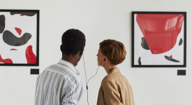 two people looking at art sharing a headphones