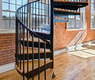 residential condo steel spiral stair with wood accents