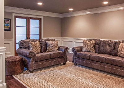 leather sofa and love seat in basement living area