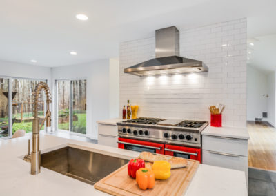 kitchen island with sink and serving board of bread and peppers