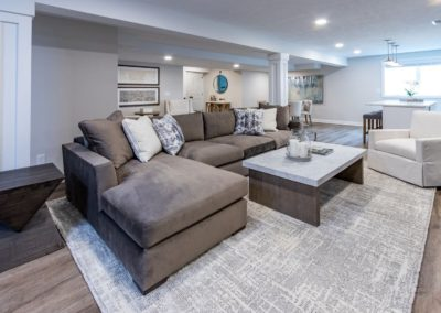 brown sectional on gray and white rug