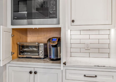 hidden cabinet in kitchen holding coffee maker and toaster oven