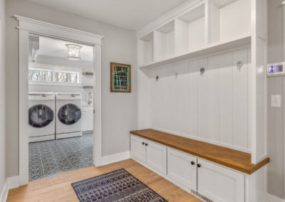 farmhouse mudroom with bench seating off of laundry room