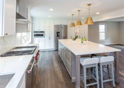 white kitchen with large storage island with seating