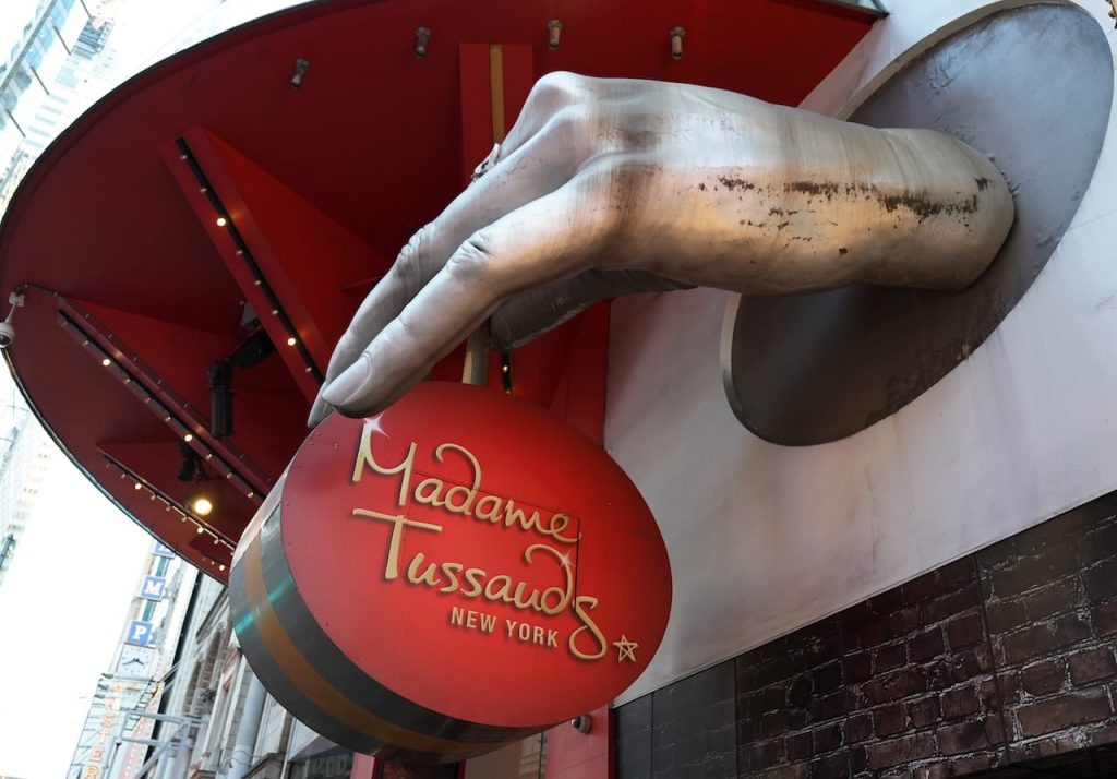 A waxed hand holding the sign of Madame Tussauds museum in New York saying its name.