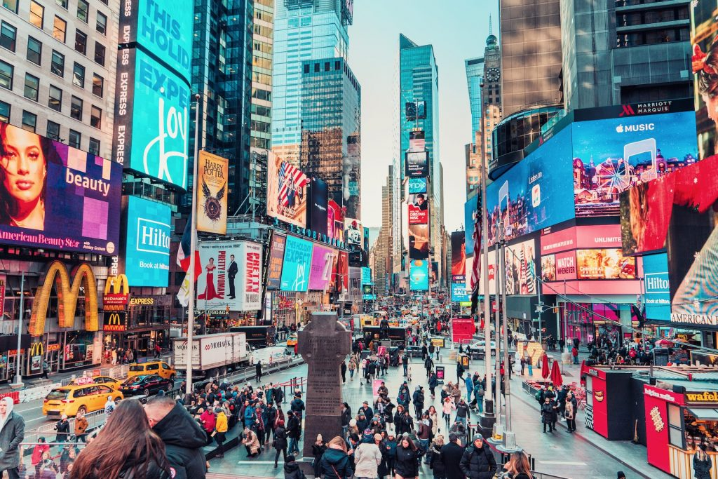 Times Square is a busy tourist intersection of neon art and commerce and is an iconic street of New York City and America.