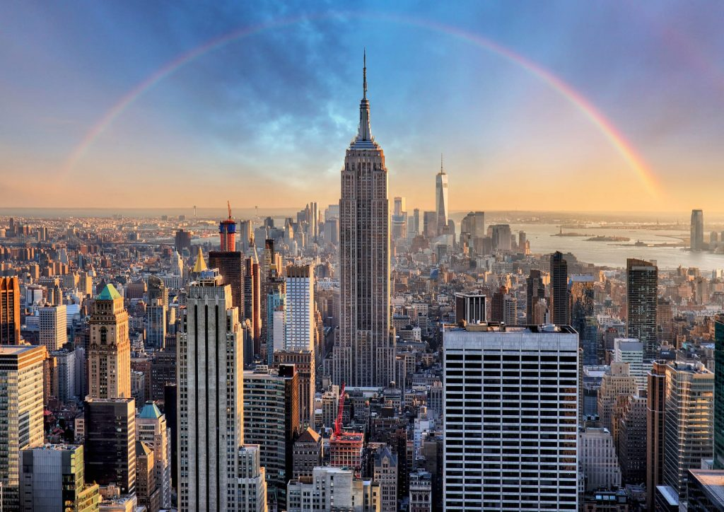 Empire state building view in New York City skyline with urban skyscrapers and rainbow.