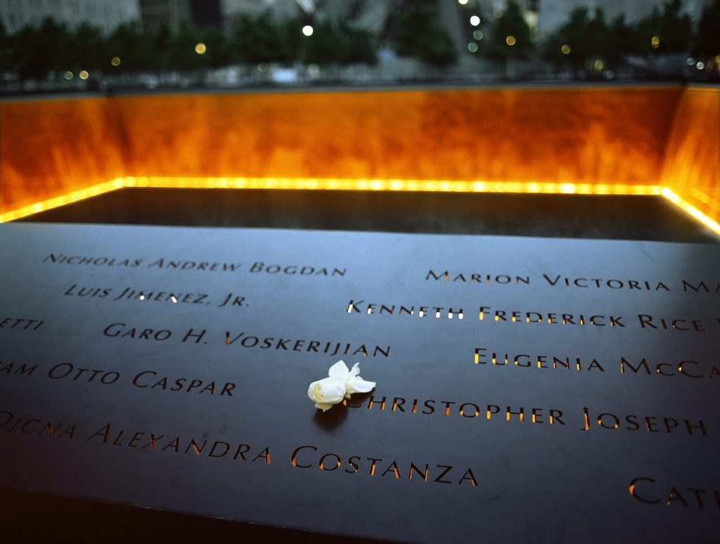 9/11 Memorial at Ground Zero, Manhattan, commemorating the terrorist attack of September 11, 2001. Flowers near the names of victims engraved in the bronze parapet.