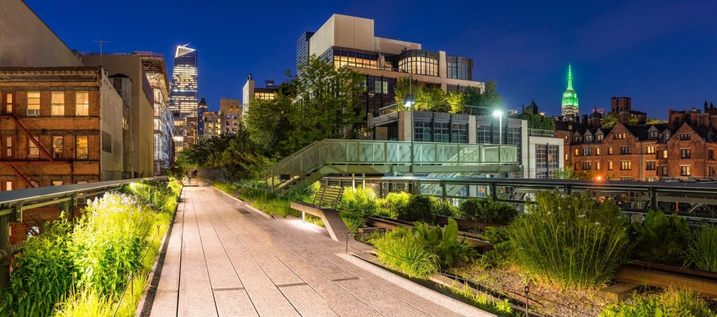 Highline panoramic view at twilight with city lights, illuminated skyscrapers and high-rises. Chelsea, Manhattan, New York CIty