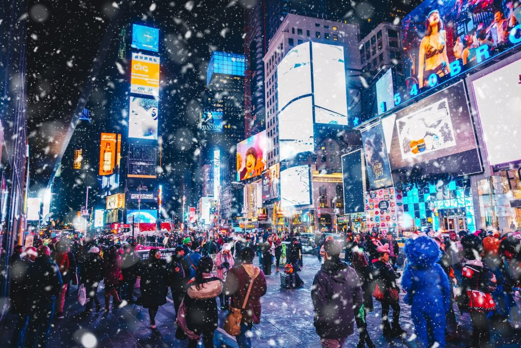 People and famous led advertising panels in Times Square during snow, one of the symbol of New York City