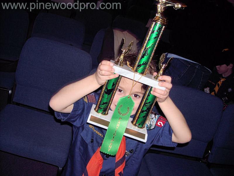 Pinewood Derby Winner Looking Through Trophy