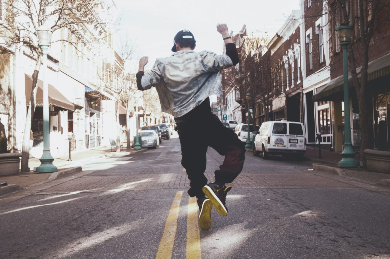Man jumping in celebration in middle of street