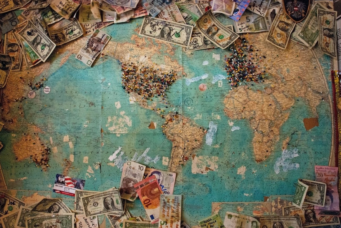 World map covered in thumbtacks and money