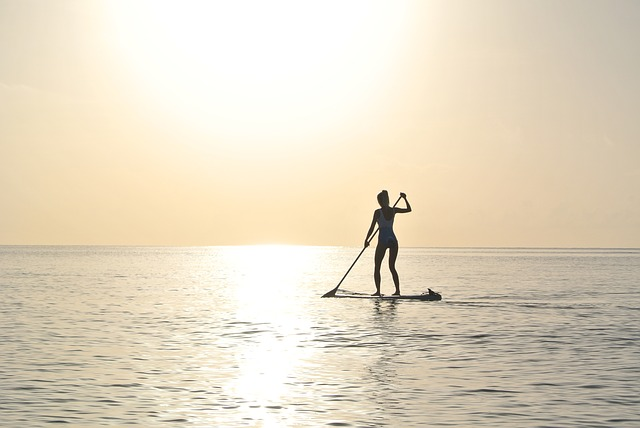 woman paddleboarding into the sunset