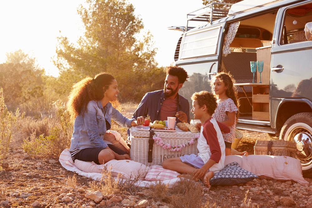 family enjoying a picnic outside an RV
