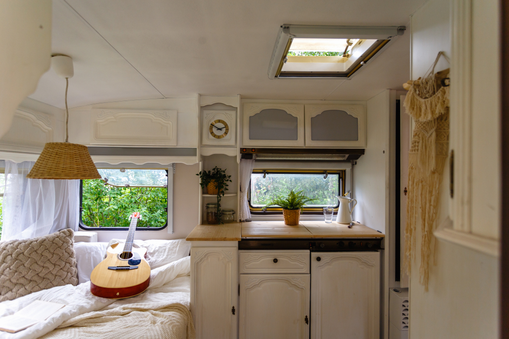 Inside a small RV - guitar rests on a bed next to a small kitchenette