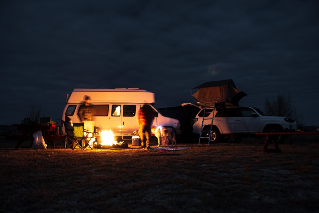 Campfire just outside a campervan