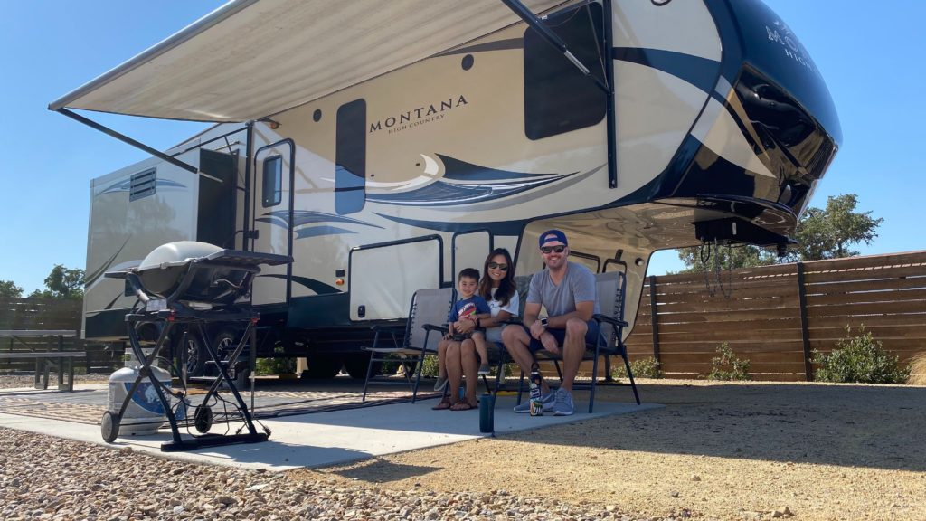 A young family at a campsite, sitting in front of large 'fifth-wheel' RV.