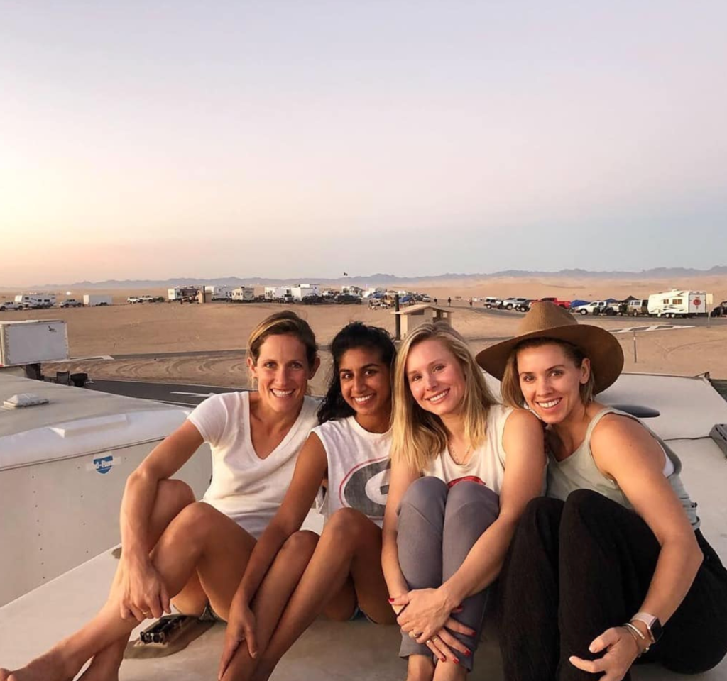 Four women, including actress Kristen Bell and Monica Padman, sit on the roof of a motorhome in desert. Other motorhomes can be seen in the background.
