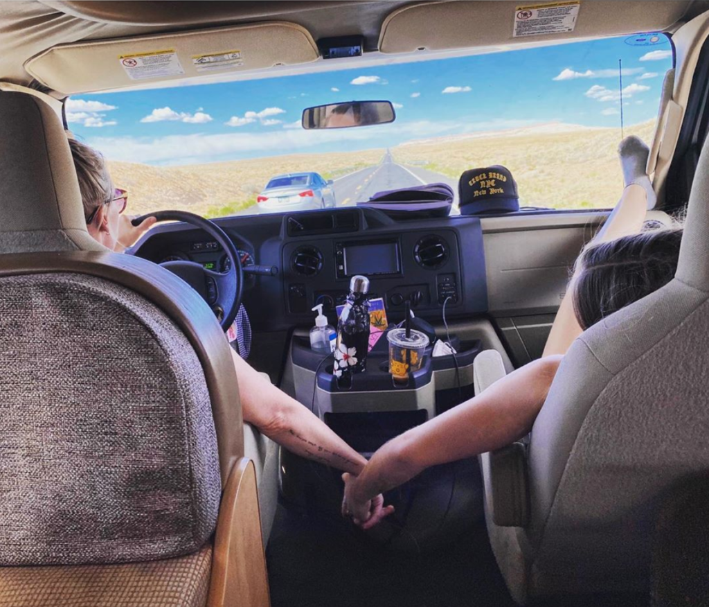 Photo taken from the back of an RV, looking out the windshield to an open two-land road. Actress Jennie Garth drives and RV while holding hands with her daughter, seated in the passenger seat with her feet rested on the dashboard.