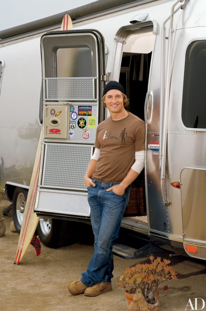 Actor Matthew McConaughey stands in the doorway of his Airstream RV. On the door are stickers and a surfboard rests against the RV.