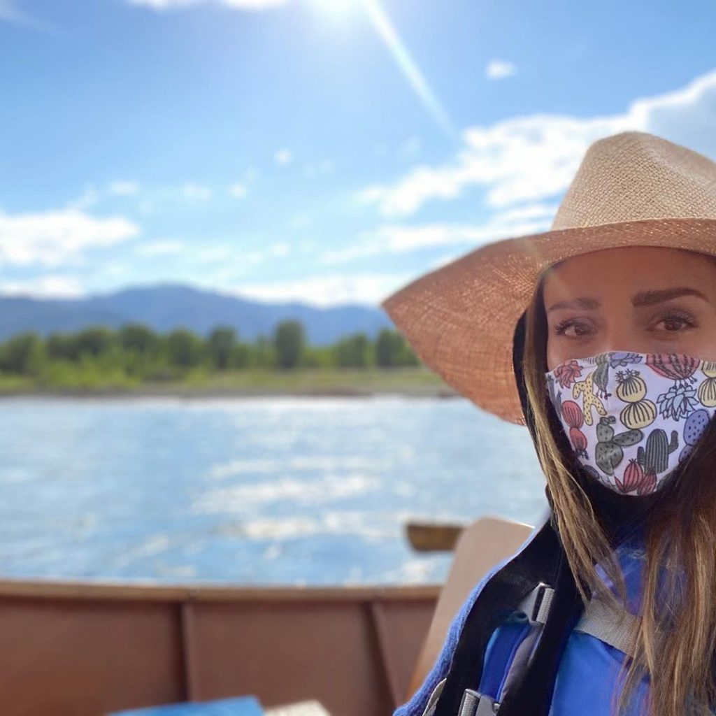 Selfie of Jessica Alba, as she sits in a boat and wears a facemask.
