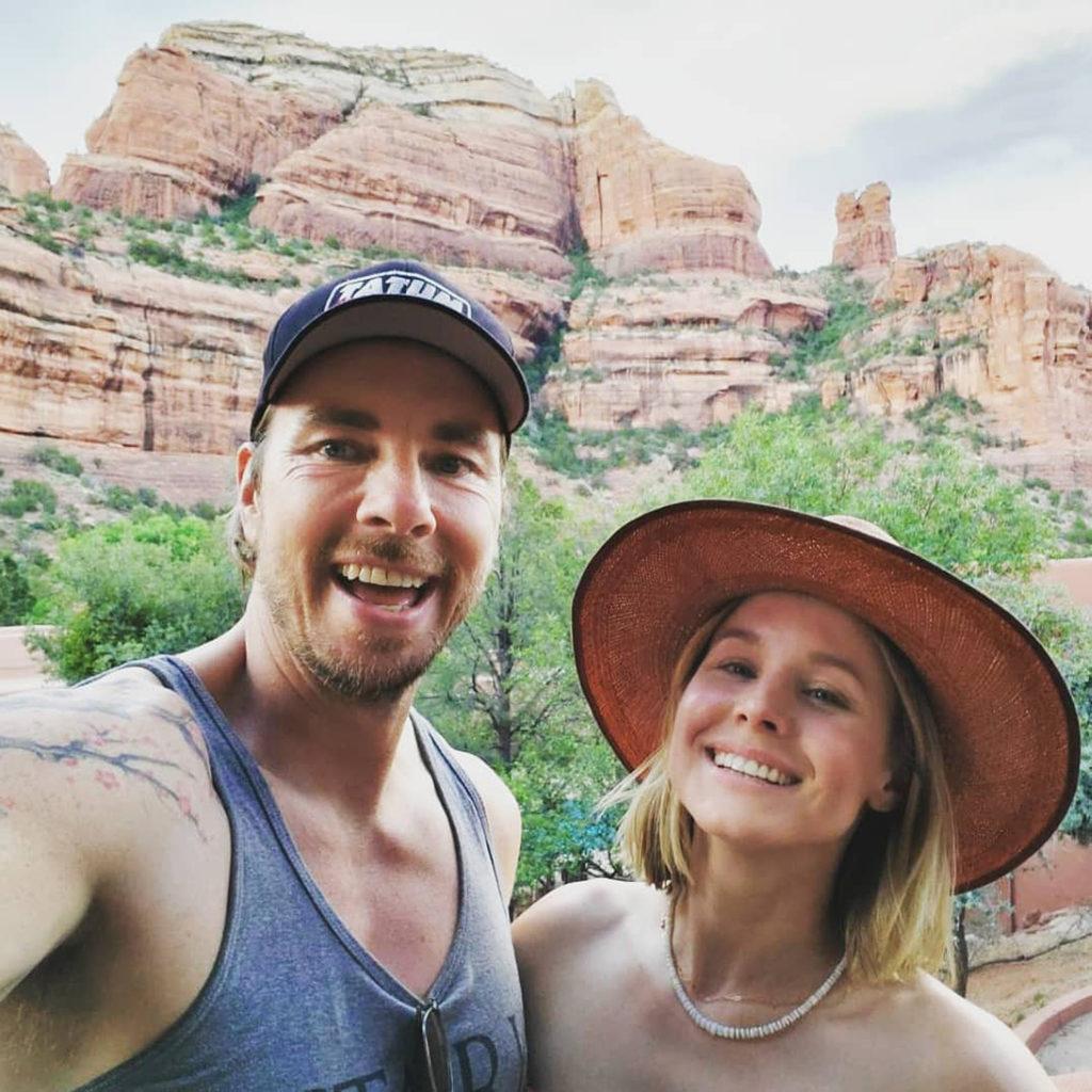 Selfie of actors Kristen Bell & Dax Shepard in front of red rock formation in Sedona, Arizona.