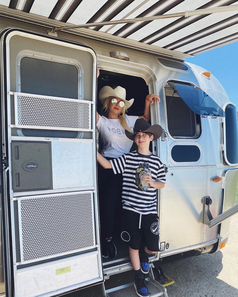 Singer Christina Aguilera and her son stand in the doorway of an Airstream RV.