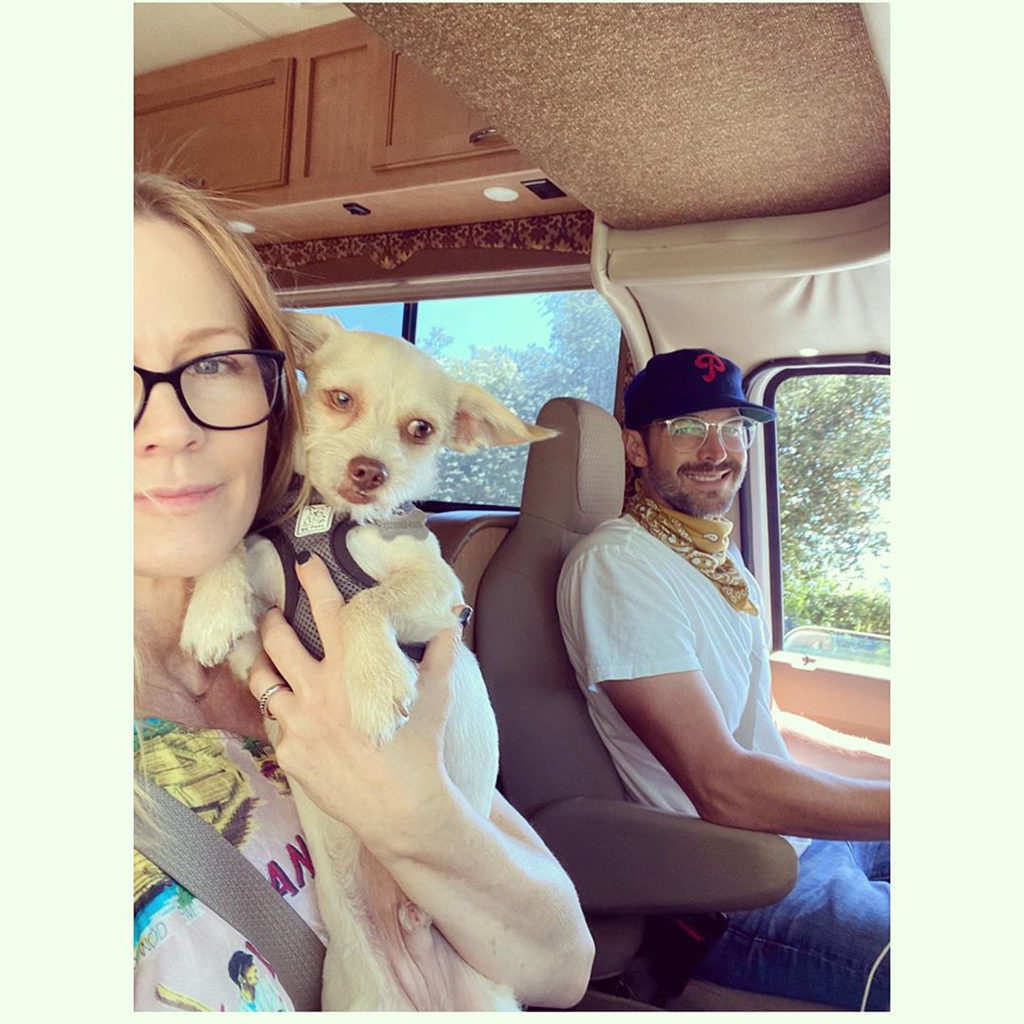 Selfie of couple while driving an RV - Actress Jennie Garth is holding a small dog and is seated in the passenger seat, and her husband is driving.