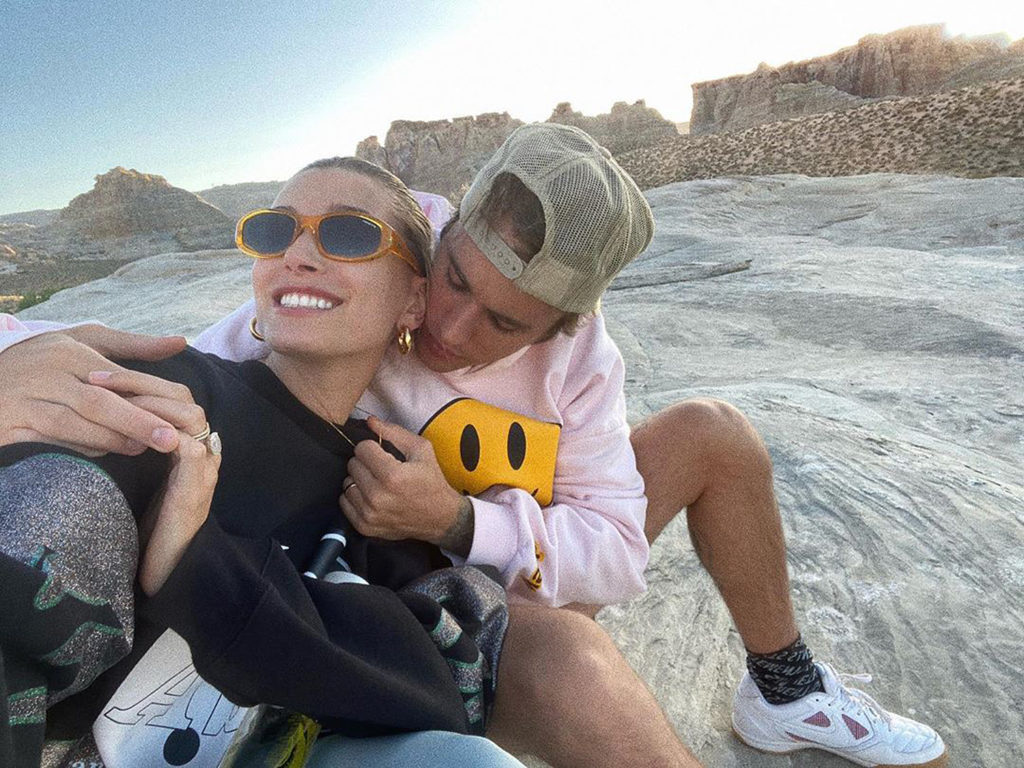 Selfie of singer Justin Bieber and his wife. They are seated with rock formations in the background.