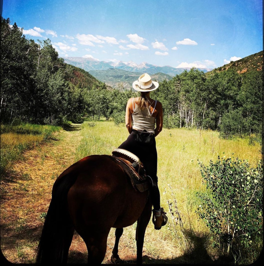 Actress Kate Hudson, while on horseback, looks towards Colorado mountains. She is in a field and facing away from the camera.