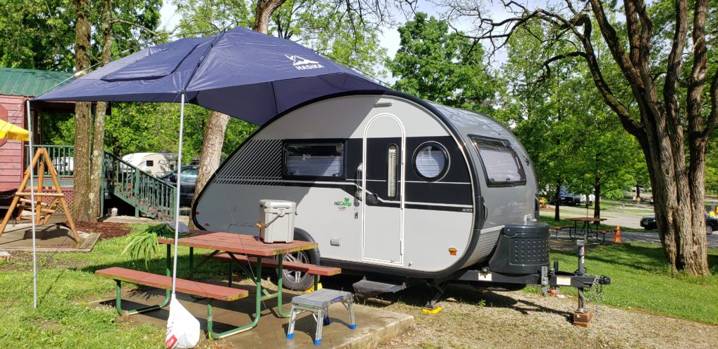 Small light grey teardrop-shaped RV with black horizontal stripe down the center. In front of RV is a wooden picnic table under an umbrella.