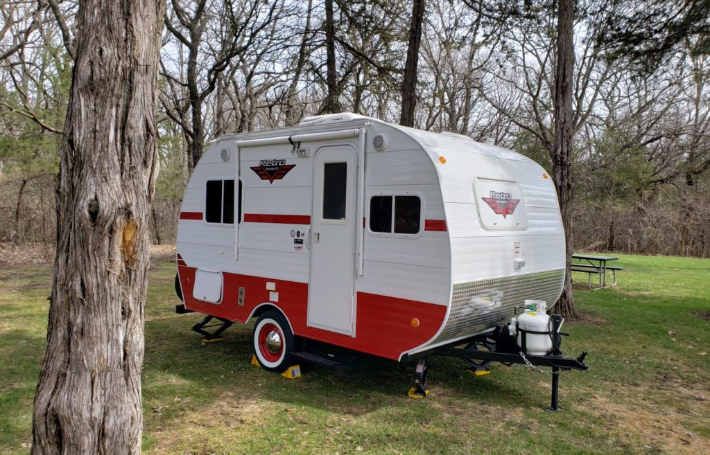 Small white and red towable RV.