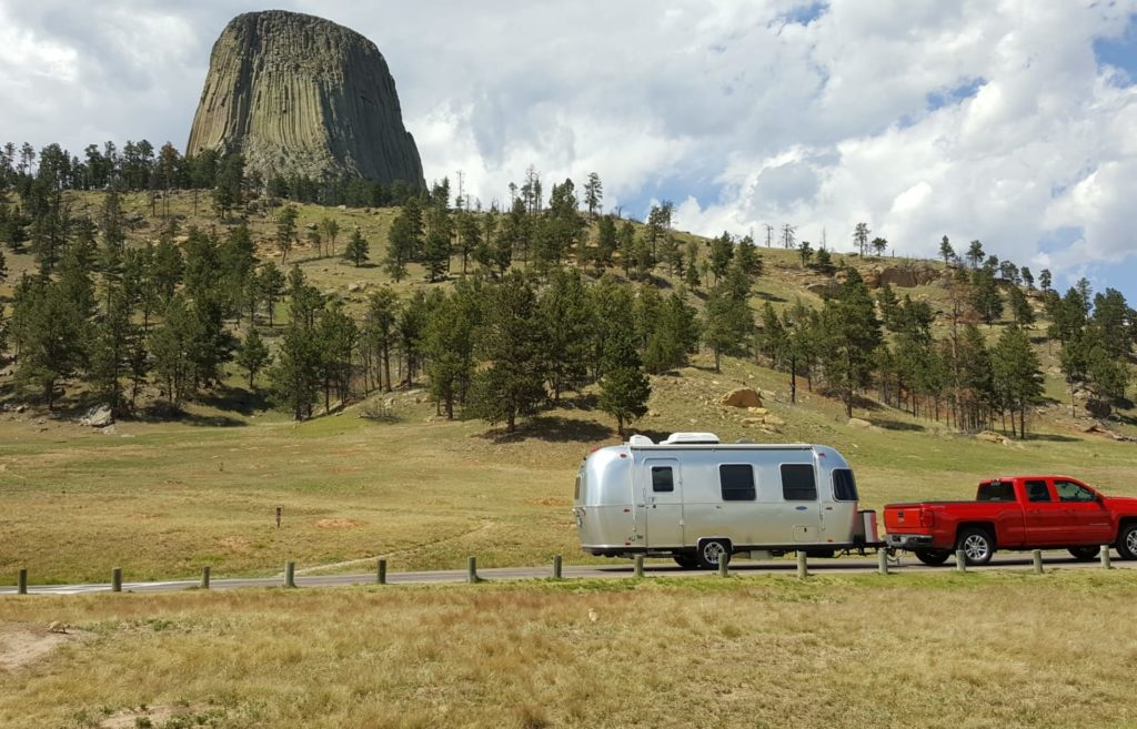 Airstream aluminum RV towed by a red pick up truck drives along mountain landscape.