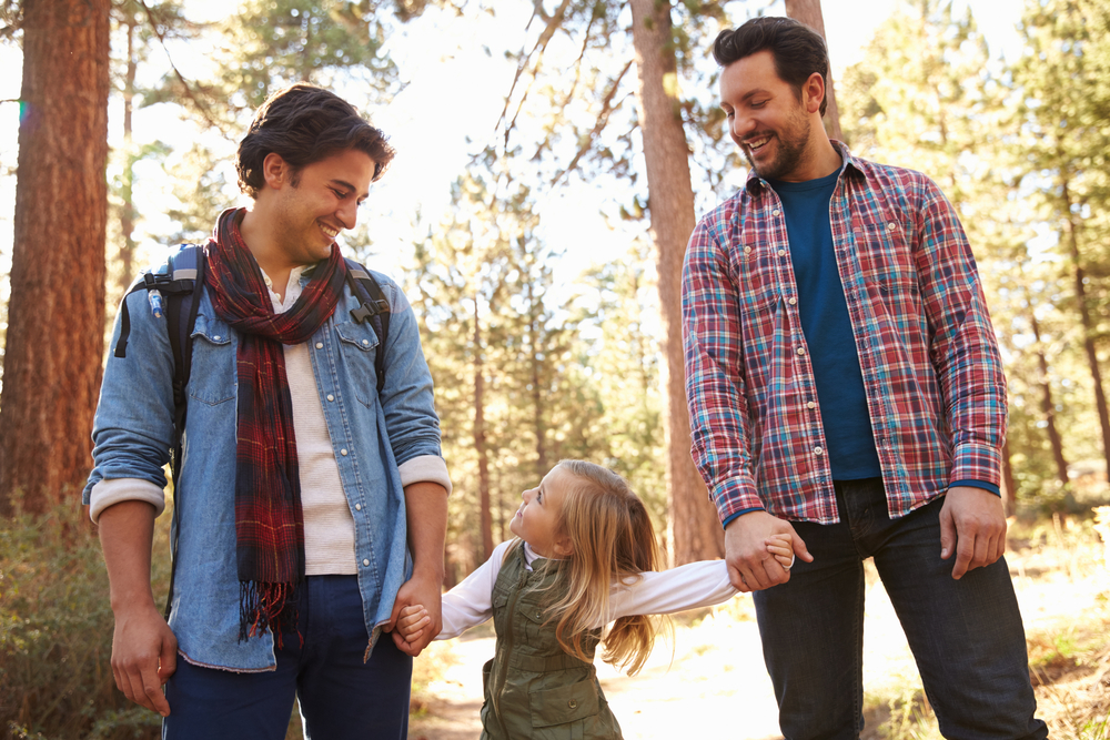 Male Couple With Daughter Walking Through Fall Woodland